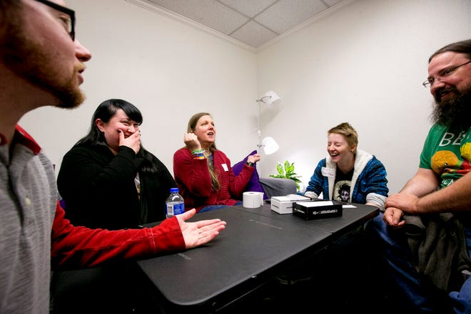 In this Thursday, Oct. 10, 2019 photo, From left, Ian Giles, founder and president of Genderbands, Christy Reed, Samantha Richardson, Mel Howarth and Mat Sillito laugh together as they all discuss the outcome of a card game during a community game night at Genderbands' office in Orem, Utah.(Isaac Hale/The Daily Herald via AP)