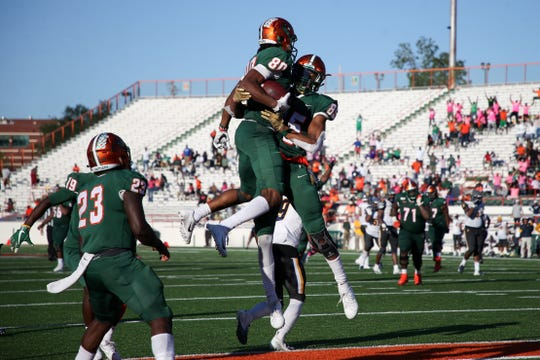 Florida A&M wide receiver Marcus Williams (80) and wide receiver David Manigo (85) celebrate after Williams scored the game-winning touchdown to defeat North Carolina A&T State 34-31 in overtime at Bragg Memorial Stadium Sunday, Oct. 20, 2019.
