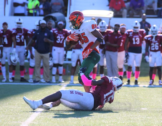 FAMU wide receiver David Manigo breaks a tackle from BJ Davis of South Carolina State.