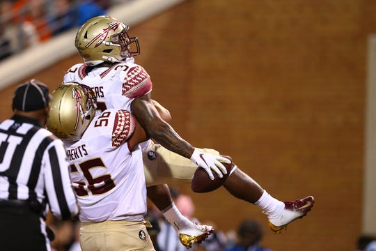 Florida State Seminoles offensive lineman Ryan Roberts (56), a Northville High graduate, lifts running back Cam Akers (3) after a touchdown in the second quarter against the Wake Forest Demon Deacons at BB&T Field during the teams' October 2019 game.