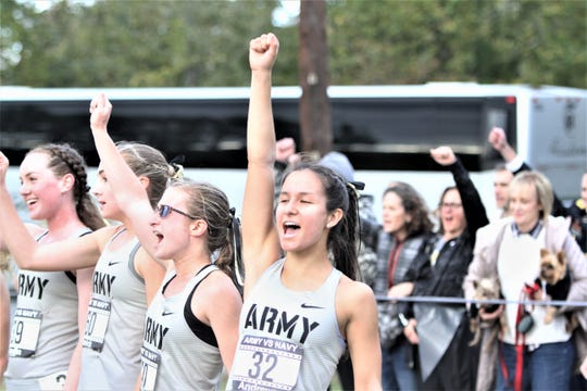 Former Dobbs Ferry standout Mika Andrews (32) hoists her fist into the air after singing Army's alma mater after her team defeated Navy by one point to win their cross-country meet at Bowdoin Park  in Wappingers Oct. 18, 2019. Andrews was the first Army finisher and was third.