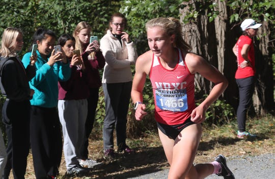 Runners take photos of North Rockland's Katelyn Tuohy as she passes on her way to winning the Girls Varsity 1 race at the Coaches Cross- Country Invitational varsity races at Bowdoin Park in Wappingers Falls  Oct. 19, 2019.