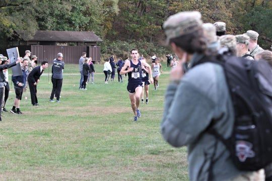 Navy's Alex Rizzo runs past Navy and Army fans as he heads to the finish of the Army vs. Navy Star Meet cross-country race at Bowdoin Park in Wappingers Oct. 18, 2019.