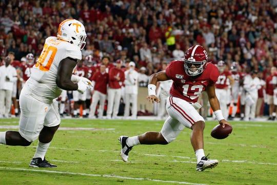 Alabama quarterback Tua Tagovailoa  scrambles around against Tennessee on Saturday in Tuscaloosa.