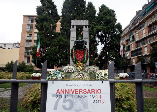 Flowers lie in front of a bronze ossuary monument entitled 'Ecco La Guerra', (Here is War) dedicated to the 'Little Martyrs of Gorla', in memory of a World War II bombing raid on Oct. 20 1944 is pictured in Milan, Italy, Sunday, Oct. 20, 2019..