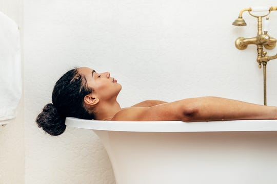 Side view of woman relaxing in a bathtub.