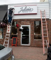 A worker puts up new sign for Julio's Pizza Co. on First Avenue in Atlantic Highlands, NJ.