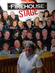 Lynn Augenstern admires the audience wall, filled with paintings of people who donated to the Goodwill Theatre, at the Schorr Family Firehouse Stage. She is a volunteer for the theater.