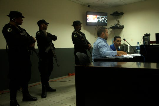 In this Oct. 11, 2019 photo, lawyer Eduardo Rubi, seated center, appears in court with his client Orlando Tercero  in Managua, Nicaragua. Tercero is accused of killing 22-year-old Binghamton University nursing student Haley Anderson in March 2018.  The court proceeding is taking place in Managua, Nicaragua, with a Nicaraguan prosecutor and a Nicaraguan judge applying that country's law. Witnesses have been testifying from Binghamton, New York via streaming video.