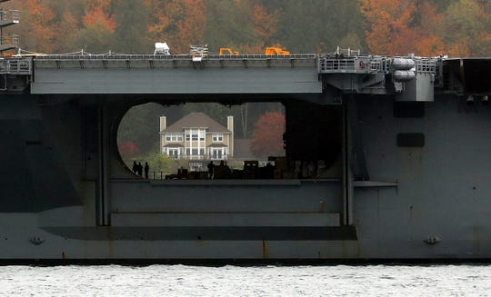 A home along the Port Orchard shoreline is framed by the hangar bay of the USS Nimitz as it passes Bachmann Park on Monday, October 21, 2019. Some residents believe the ship is responsible for radio interference causing remote-less entry devices to go on the fritz; the Navy denies that claim.