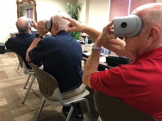 Lou Seiler, pointing, Space Coast Honor Flight videographer, Stu Glass, marketing and public relations director for Space Coast Honor Flight, center, and Space Coast Honor Flight president Jim Hart watch the virtual reality tour of a recent Honor Flight trip to Washington D.C.