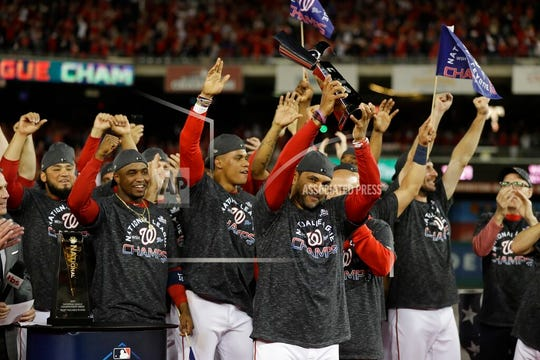 Washington Nationals manager Dave Martinez raises the NLCS trophy after Game 4 of the baseball National League Championship Series against the St. Louis Cardinals Tuesday, Oct. 15, 2019, in Washington. The Nationals won 7-4 to win the series 4-0.