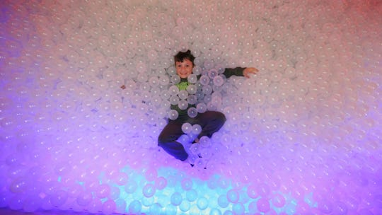 A boy plays in a giant ball pit located in the center of 'Worst-Case Scenario Survival Experience' at the Franklin Institute.