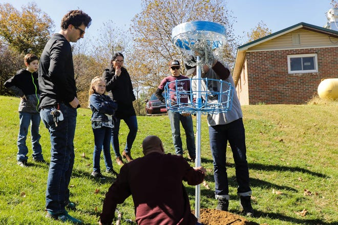 Employees from the Chillicothe Parks and Recreation department, along with members of Project Bad Apple, place the first basket for the city's new disc golf course.