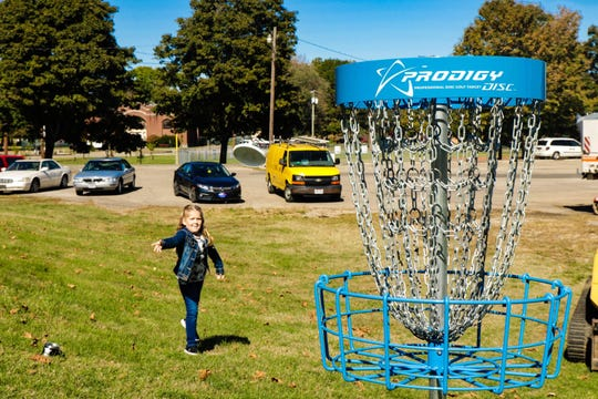 Madison Cline practices throwing a disc into the first basket installed as part of the new Yoctangee Park disc golf course, created by Project Bad Apple.
