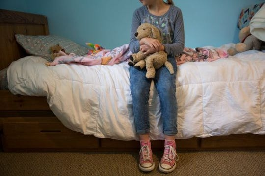 A little girl who's been in and out of foster care sits on a bed at St. Joseph's Orphanage in 2018.