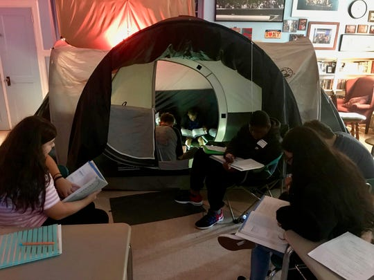Students at Soehl Middle School in Linden sitting inside and around a tent in teacher Jan Macha's language arts class. Macha put up the tent to add atmosphere for lessons on horror literature.