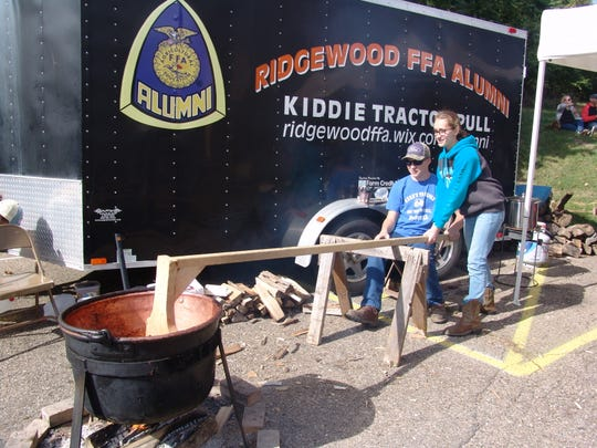 Ridgewood FFA members Mason Mizer, seated, and Alivia Mourer take turns stirring apple butter during the 49th annual Apple Butter Stirrin' Festival.