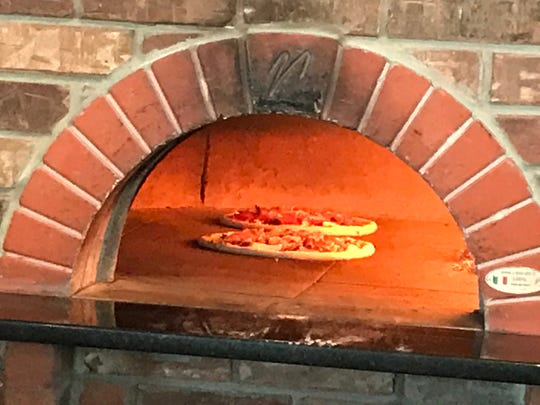 Neapolitan pies back at 800 degrees in a special imported Italian oven fired with red oak at Pyra Pizzeria in Norwalk.