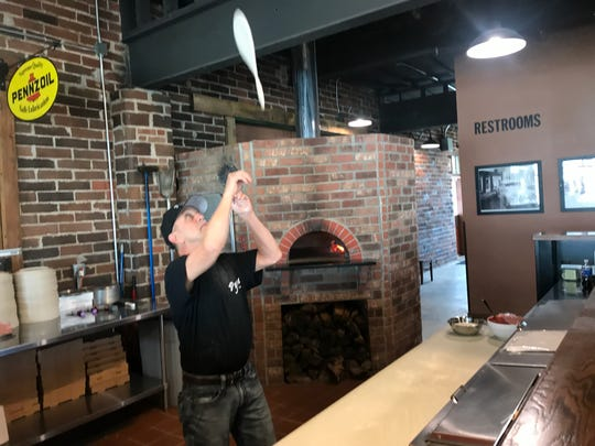Kirby Brown, 62, head pizzaiolo and semi-retired financial reporting and compliance officer, tosses pizza dough into the air at Pyra Pizzeria in Norwalk.