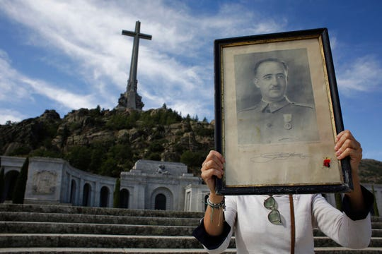 In this Friday, Oct. 4, 2019 photo, a visitors holds a portrait of former Spanish dictator Francisco Franco at the Valley of the Fallen mausoleum near El Escorial, outskirts of Madrid, Spain.