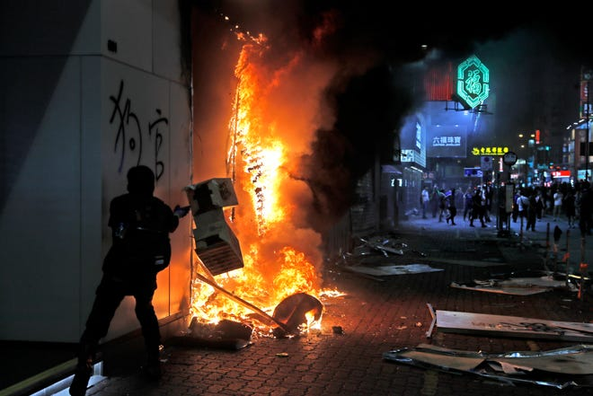 Protesters set fire to a Xiaomi shop at Nathan road in Hong Kong, Sunday, Oct. 20, 2019.