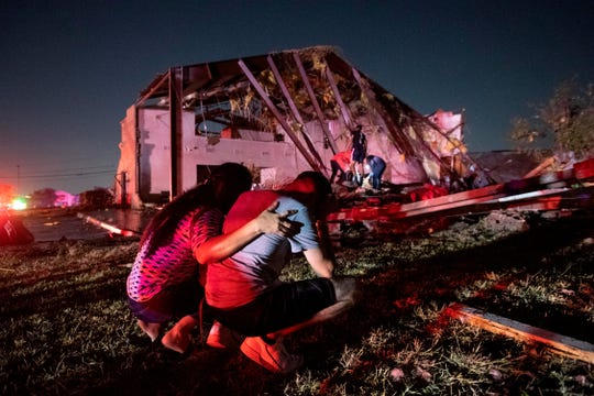 In this Sunday, Oct. 20, 2019 photo, Henry Ramirez, a member of Primera Iglesia Dallas, is consoled by his mother Maribel Morales as they survey severe damage to the church, where Ramirez plays drums and Morales attends, after a tornado tore through North Dallas.
