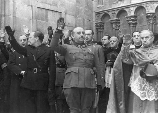 In this Nov. 20, 1938 file photo, former Spanish dictator Francisco Franco, center, attends the second anniversary of the death of Jose Antonio Primo de Rivera, the founder of the Spanish right-wing movement La Falange, in Burgos, Spain.
