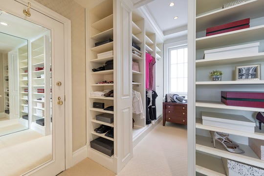 Custom built-ins help maximize the space in this walk-in closet.