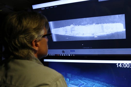 In this Wednesday, Oct. 16, 2019, photo, Vulcan Inc. director of subsea operations on the Petrel, Rob Kraft, left, looks at images of the Japanese aircraft carrier Kaga.