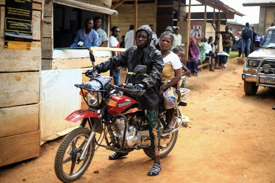Motorcycle taxi driver Germain Kalubenge transports a woman whose 5-year-old daughter had a fever and was vomiting to an Ebola transit center where potential cases are evaluated, in Beni, Congo, Thursday, Aug. 22, 2019.