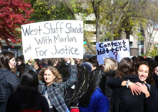 Students and faculty from Madison West High School, including teacher Sarah Quinn, with sign, rally in support of the school's recently-fired security guard Marlon Anderson outside the Doyle Administration Building in Madison, Wis. Friday, Oct. 18, 2019.