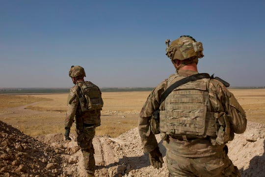 In this Sept. 6, 2019 file photo, U.S. soldiers survey the the safe zone between Syria and the Turkish border near Tal Abyad, Syria. Defense Secretary Mark Esper said Monday the U.S. is considering leaving some troops behind to secure oil fields in the region and make sure they don't fall into the hands of a resurgent Islamic State.