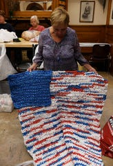 "Donna Harki of Lincoln Park shows one of the crocheted mats that she made from ""plarn"" with a pocket (in blue) where clothing can be put and used as a pillow at the Bacon Memorial District Library in Wyandotte. The Bag Ladies with a Cause meet Tuesday evenings to make ""plarn"" from plastic bags and crochet them into mats for homeless."