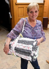 "Donna Harki of Lincoln Park shows one of the crocheted mats made from ""plarn"" with a carrying strap at the Bacon Memorial District Library in Wyandotte. The Bag Ladies with a Cause meet Tuesday evenings to make ""plarn"" from plastic bags and crochet them into mats for homeless."