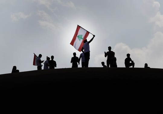 """Anti-government protesters wave a Lebanese flag, as they stand on the Dome City Center known as """"The Egg,"""" an unfinished cinema leftover from the civil war, as they watch other protesters, in downtown Beirut, Lebanon, Sunday, Oct. 20, 2019."""