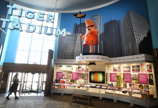 A familiar Little Caesars Pizza character towers over the display in the Allesee Gallery of Culture at the Detroit Historical Museum.