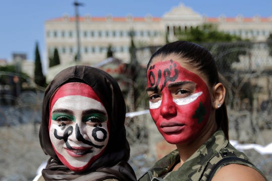 """Anti-government protesters with the colors of the Lebanese national flag painted on their faces and with Arabic that reads """"Revolution,"""" pose for a photograph in front of the government palace in Beirut, Lebanon, Monday, Oct. 21, 2019."""