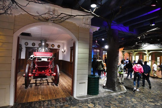 """Museumgoers pass an old firehouse created in """"The Streets of Old Detroit"""" hall at the Detroit Historical Museum."""