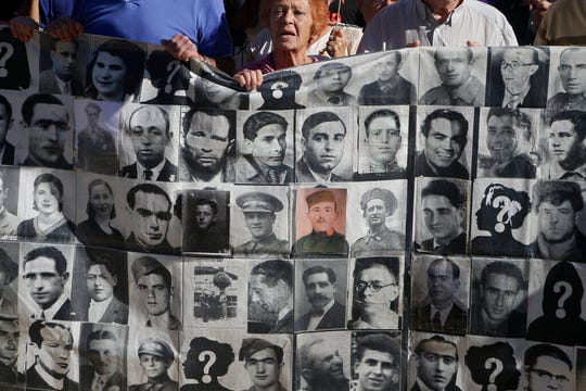 Protesters hold a banner showing photos of Spanish Civil War victims, outside the Supreme Court in Madrid, Spain, Tuesday, Sept. 24, 2019.