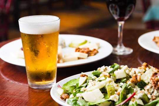 Icy cold beer with salad and appetizer dishes and red wine.