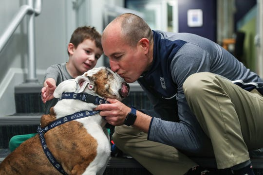 From right, handler Michael Kaltenmark kisses Butler Blue III, also known as Trip, while posing for photos at Butler University's Robertson Hall in Indianapolis, Monday, Oct. 21, 2019. Kaltenmark's 5-year-old son Miles is seen at left. Michael and Trip will retire at the end of the 2019-2020 academic year.