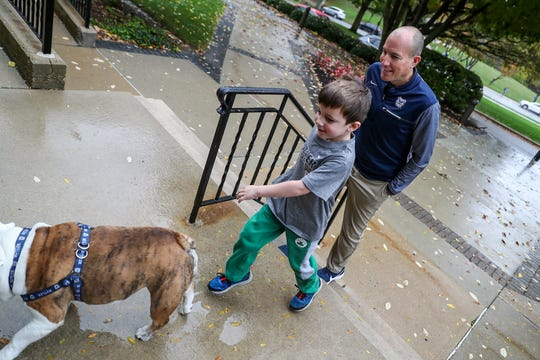 From right, Michael Kaltenmark, his son Miles Kaltenmark, 5, and Butler Blue III, also known as Trip, return from taking Trip for a potty break at Butler University in Indianapolis, Monday, Oct. 21, 2019.
