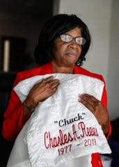 Delores Fatherree holds the embroidered throw from her 42-year-old son Charles Reeves II's funeral.