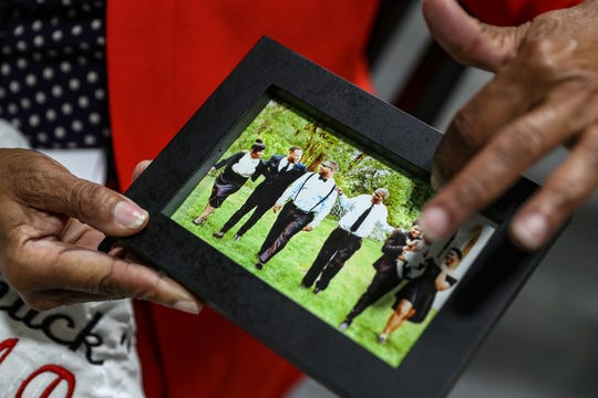 """Delores Fatherree holds a picture of her 42-year-old son Charles Reeves II, third from left, with family, in Indianapolis, Tuesday, Oct. 15, 2019. In May, Reeves was killed in the crossfire of a shooting while walking to his car. Fatherree has since spoken at interventions held by the Indianapolis Office of Public Health for people who have been linked to recent shootings. """"Because of somebody's senseless behavior, my son lost his life,"""" Fatherree said."""