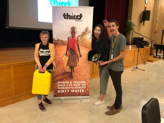 Spencer-Van Etten student Phoebe Delmage-Brodie holds a five-gallon jerry can for hauling water, alongside Mikayla Martinez and Paul Rivas, of the Thirst Project.