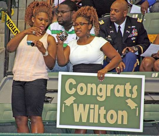 "Wilton Jackson's sisters, Lauren and Natasha, attend his graduation ceremony in May 2011 at the Mississippi Coliseum, as does his dad, Lt. Col. Wilton ""Chuck"" Jackson, right."