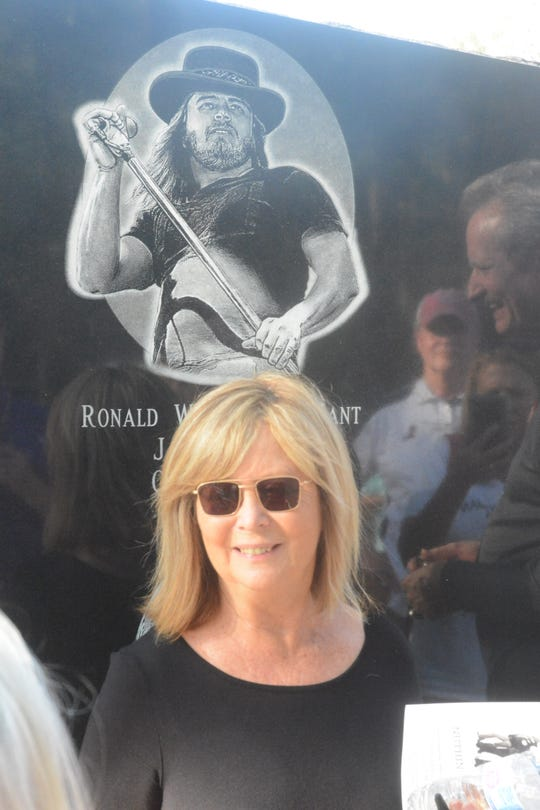 Judy Van Zant-Jenness stands below a sketch of her Ronnie Van Zant, the original lead singer of the Southern rock band, Lynyrd Skynyrd. The sketch is part of a monument to the band members who lost their lives following a plane crash near Gillsburg, Miss., on Oct. 20, 1977. Van Zant-Jenness, his widow, helped unveil the monument at a ceremony on Oct. 20, 2019.