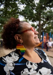 Maria Velasquez  smiles while wearing her custom earrings to support the LGBTQ community at the 2019 Jackson Pride Fest at Conger Park in Jackson, Tenn., Saturday, Oct. 19, 2019.