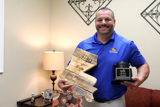 Toby Armentor of DJW Insurance holds two of the office's recent trophies from the REALTOR Association of Acadiana's Gumbo Cook-Off.